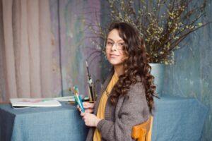freelance artist on her work station holding art materials