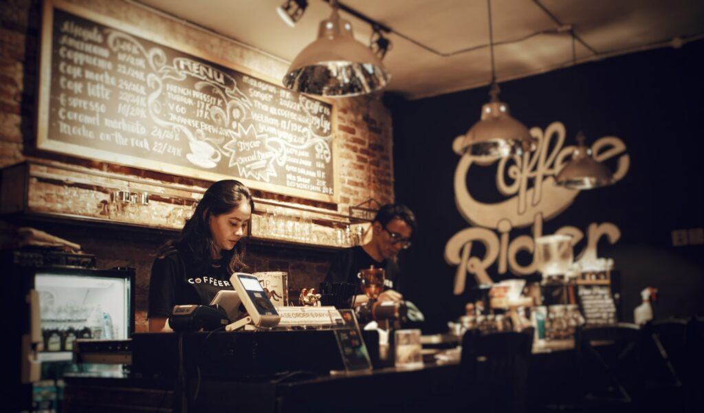 coffee shop staff members fulfilling the role of cashiers, which involves having a good cashier job description to succeed in their line of work