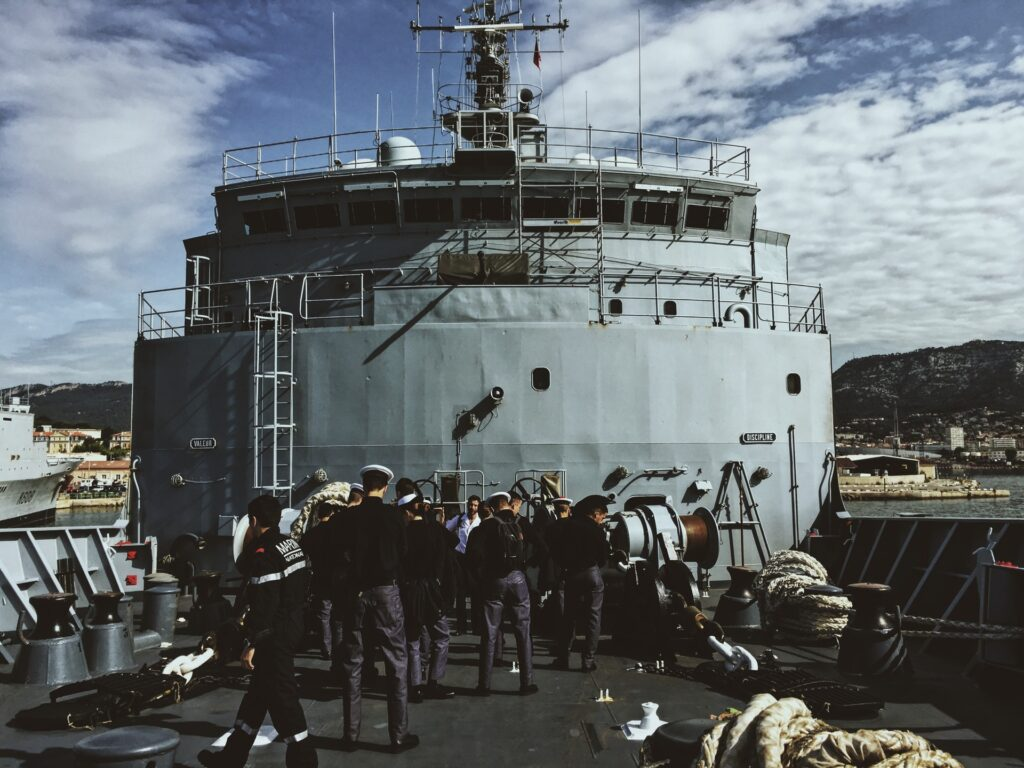 Photo of a ship with the crew in front of it, which signifies the need for strong chief mate resume examples reflecting a chief mate's leadership