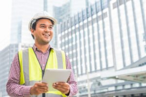 Man wearing hard hat holding a tablet showing construction project manager resume
