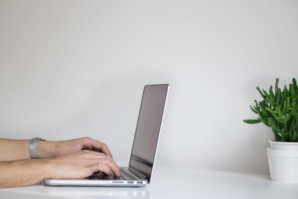 a person looking for a resume sample online using laptop