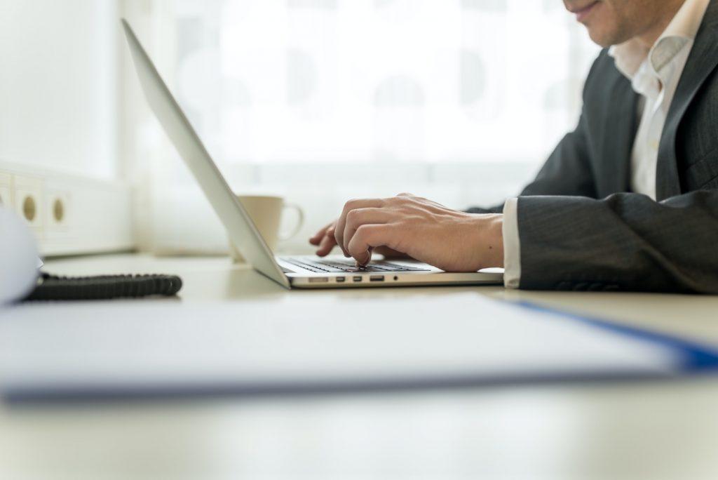 job seeker typing his resume on laptop