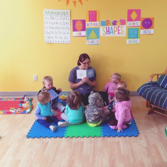 teacher teaching nursery students in a classroom